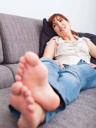 female feet: Beautiful young woman at home sitting on sofa and relaxing