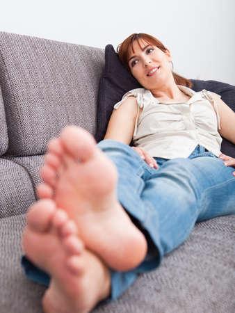 mujeres sentadas: Hermosa mujer joven en casa sentado en el sof� y relajante Foto de archivo