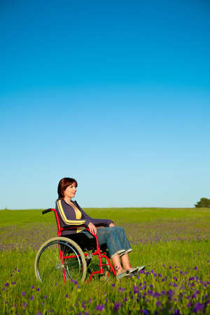 Handicapped woman on a wheelchair over a green meadow  photo