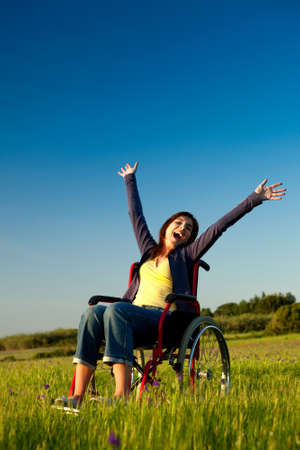 disabled people: Happy handicapped woman on a wheelchair over a green meadow