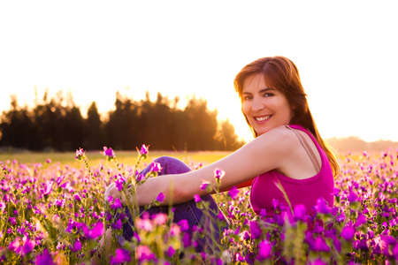 Beautiful young woman sitting on a flowery meadow Stock Photo - 7199388
