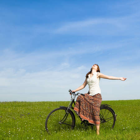 Happy young woman with a vintage bicycle on a green meadow Stock Photo