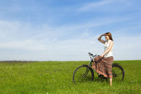 Happy young woman with a vintage bicycle on a green meadow Stock Photo - 7199954
