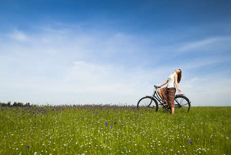 Happy young woman with a vintage bicycle on a green meadow photo