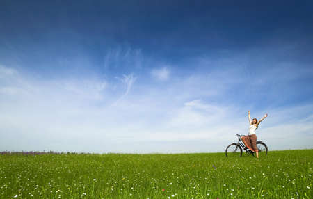 Happy young woman with a vintage bicycle on a green meadow Stock Photo - 7199821