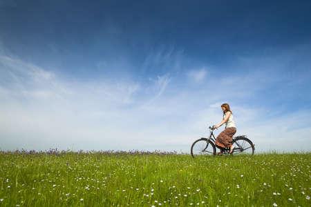bicicleta retro: Joven feliz en un prado verde, andar en bicicleta