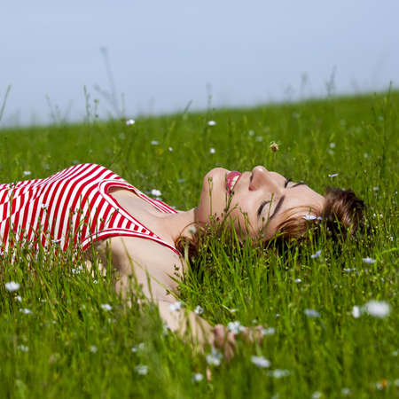 Young woman relaxing on a beautiful green meadow photo