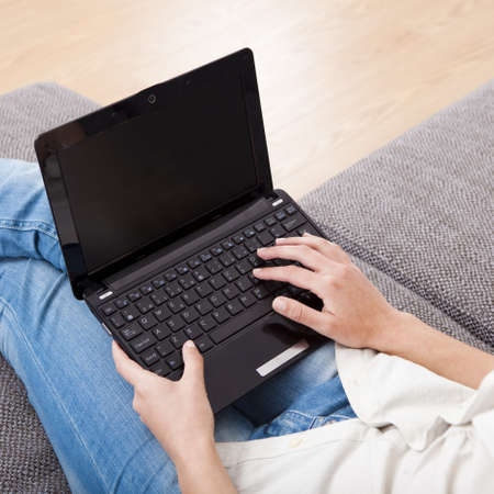 woman couch: Young woman at home seated on sofa and working with a laptop