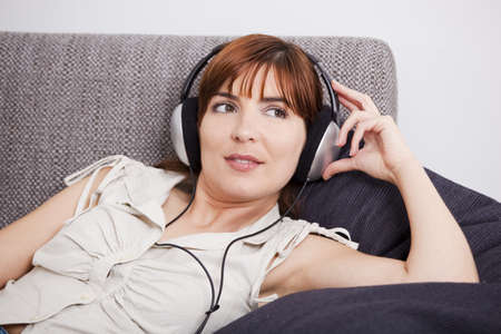 Beautiful young woman at home listening music with headphones photo
