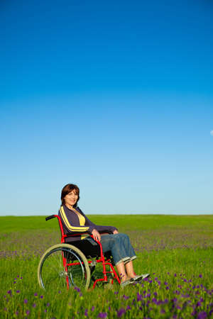 Handicapped woman on a wheelchair smiling over a green meadow  Stock Photo