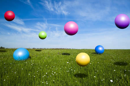 Colored balls jumping on a green meadow photo