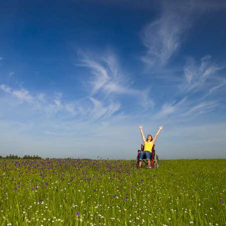 Happy behinderte Frau auf einen Rollstuhl über eine grüne Wiese