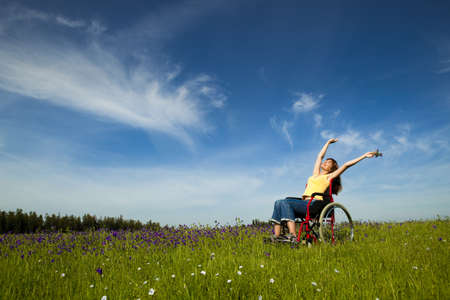 arm chairs: Happy handicapped woman on a wheelchair over a green meadow