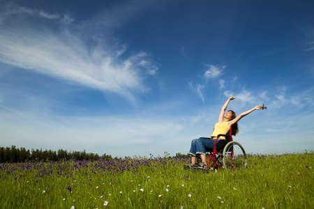 discapacidad: Mujer con discapacidad feliz en una silla de ruedas en un prado verde