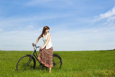 Young woman with a vintage bicycle on a green meadow photo