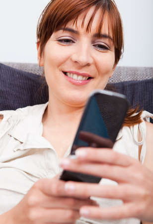 Portrait of a beautiful woman seated on sofa holding a cellphone and sending a sms photo