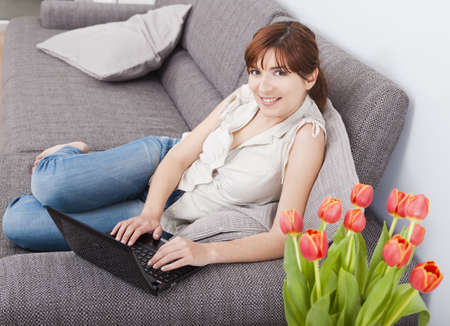 Beautiful woman at seated on sofa and working with a laptop photo