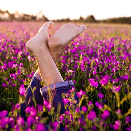 piernas mujer: Femeninas las piernas cruzadas en un hermoso prado florido  Foto de archivo
