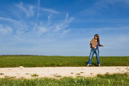 Young woman hitch hiking on a beautiful green meadow photo