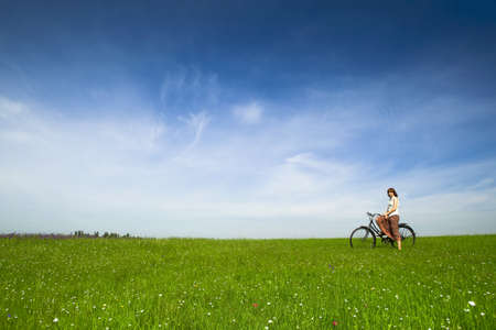 Happy young woman with a vintage bicycle on a green meadow Stock Photo - 7326015