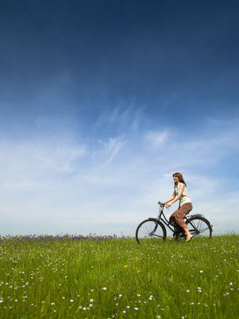 Happy young woman on a green meadow riding a bicycle photo