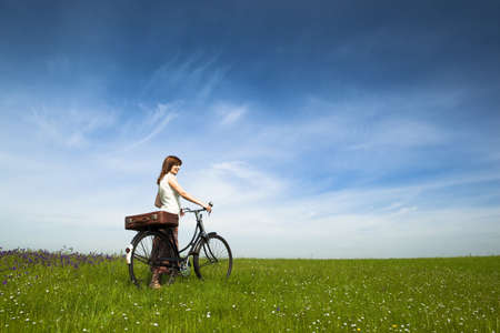 free riding: Happy young woman on a green meadow with a vintage bicycle