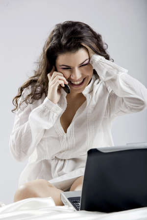 Beautiful young woman sitting on bed working with a laptop and making a phone call Stock Photo - 7413404