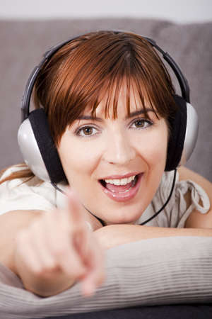 Young woman looking to you and pointing while listening music photo