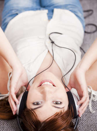 Top view of a beautiful young woman listening music with headphones photo