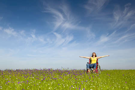 handicapped person: Happy handicapped woman on a wheelchair over a green meadow