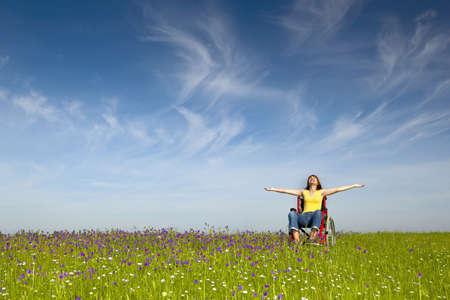 discapacitados: Mujer con discapacidad feliz en una silla de ruedas en un prado verde