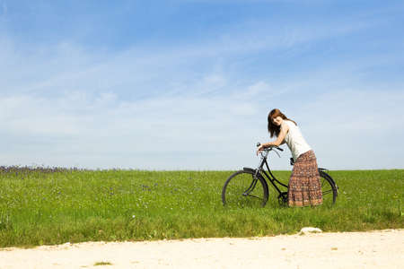 Happy young woman with a vintage bicycle on a green meadow Stock Photo - 7413426