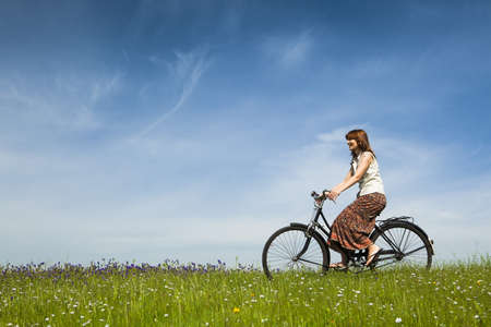 free riding: Happy young woman on a green meadow riding a bicycle