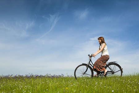 retro bicycle: Mujer joven feliz en un prado verde, andar en bicicleta