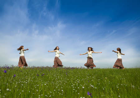 Same young woman in diferent positions dancing on a beautiful green meadow photo