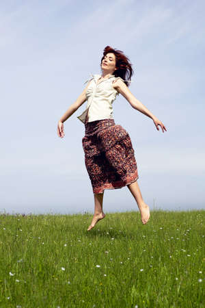 Young woman jumping on a beautiful green meadow photo