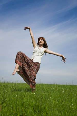 Young woman making dancing poses on a beautiful green meadow photo