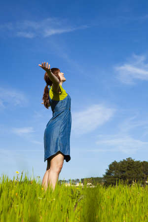 Beautiful happy woman on a green meadow with arms open Stock Photo - 7508492