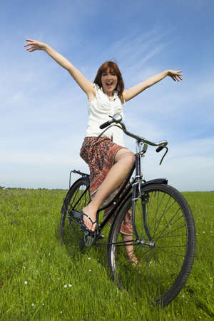 Happy young woman relaxing over a vintage bicycle photo