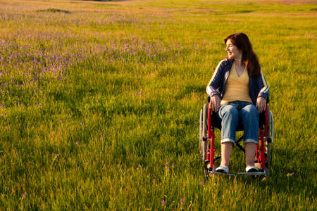 wheel chair: Happy handicapped woman on a wheelchair over a green meadow looking away Stock Photo