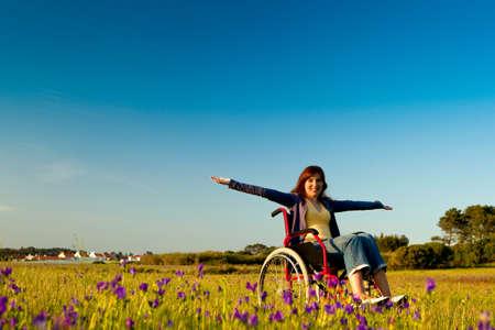 persona en silla de ruedas: Mujer con discapacidad feliz en una silla de ruedas en un prado verde