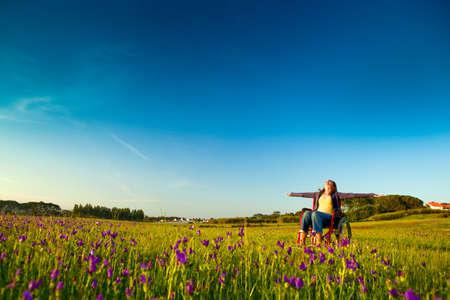緑の牧草地で車椅子に幸せな障害を持つ女性