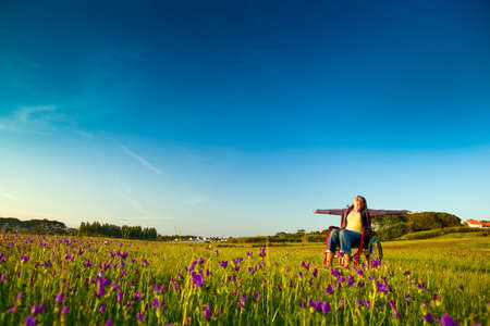 Happy handicapped woman on a wheelchair over a green meadow Imagens - 7636848