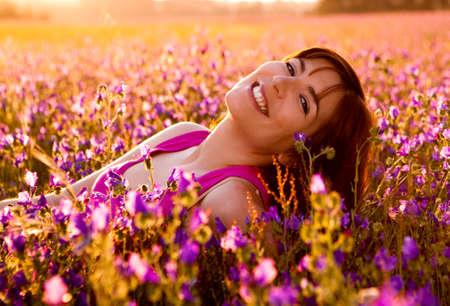 lying in grass: Joven y bella mujer acostado en un prado florido  Foto de archivo