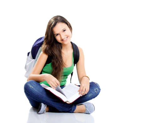 Beautiful young female student sitting on floor studying, isolated on white photo