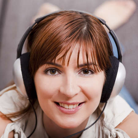 Close-up portrqit of a beautiful young woman listening music with headphones Stock Photo - 7750738