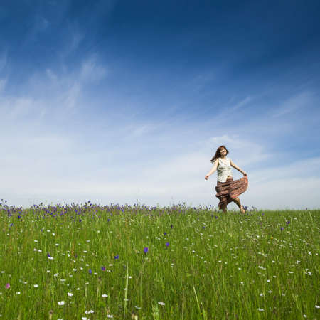 people in nature: Young woman dancing on a beautiful green meadow