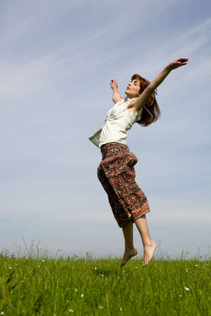 grass skirt: Young woman jumping on a beautiful green meadow