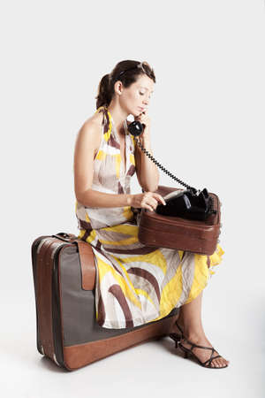 Beautiful young fashion woman sitting over a suitcase and making a phone call photo