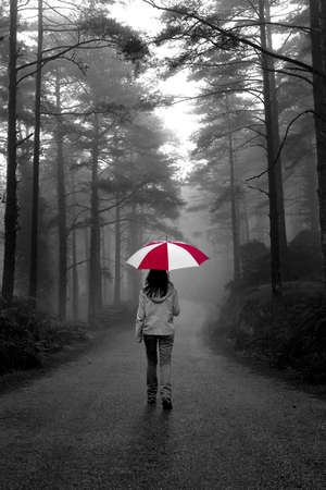people walking street: Girl walking with an umbrella on a winter rainy day